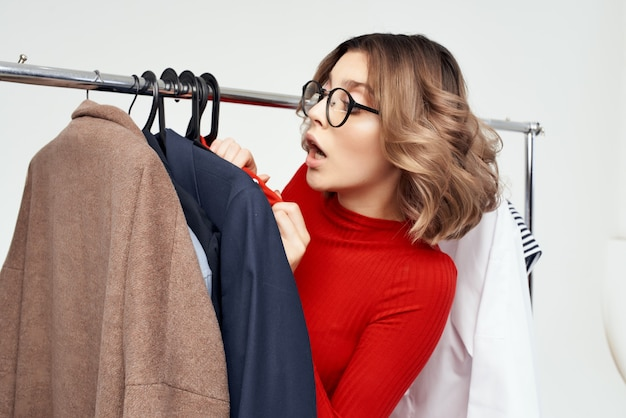 Pretty woman in a red jacket near the wardrobe retail isolated background. high quality photo
