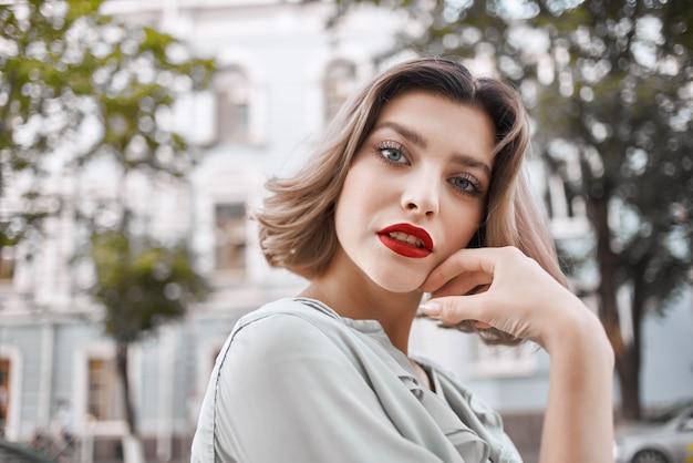 Pretty woman red lips charm outdoors closeup