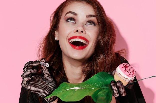 きれいな女性の赤い唇緑の葉の薬ピンクの背景