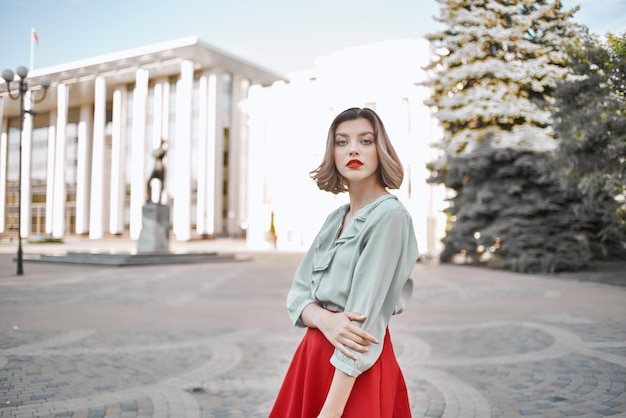 Pretty woman in red skirt walking in the city outdoors