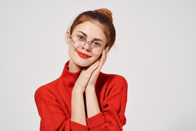 Pretty woman red sweater hand gesture glasses red lips isolated background. high quality photo