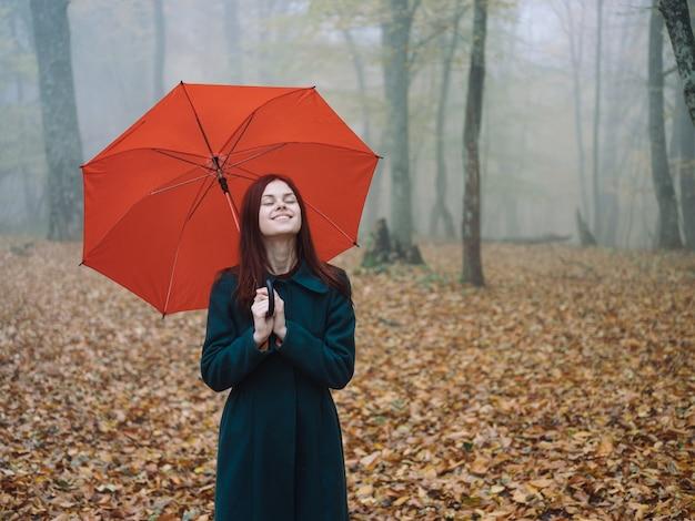 きれいな女性の赤い傘は霧の黄色の葉と森の中を秋に歩きます