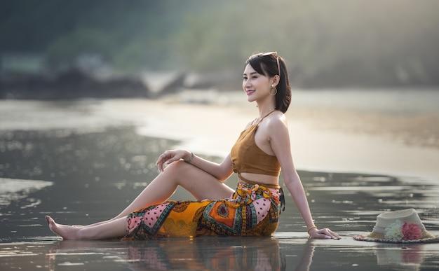 美しい女性は、熱帯のビーチでリラックスしています。遠隔の熱帯のビーチと国。旅行のコンセプト。
