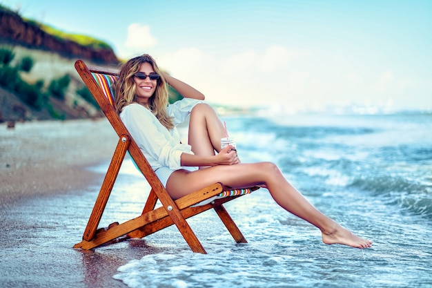 Pretty woman relaxing on a lounger beach and drinks soda water