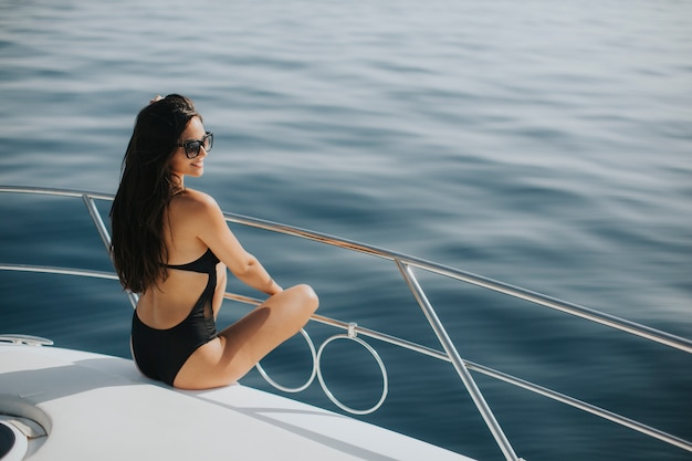 Pretty woman relaxing on the yacht on sea at sunny day