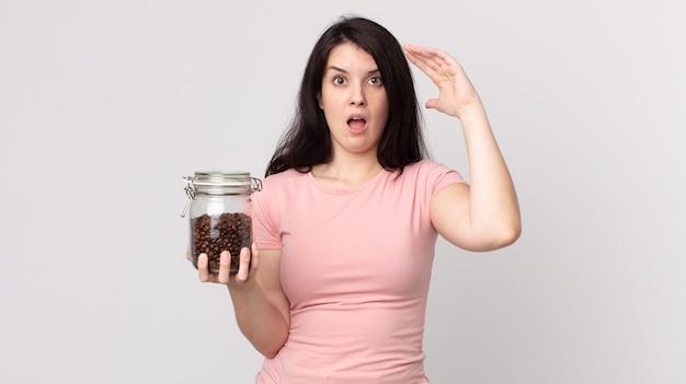 공중에 손을 들고 비명을 지르는 예쁜 여자와 커피 콩 병을 들고