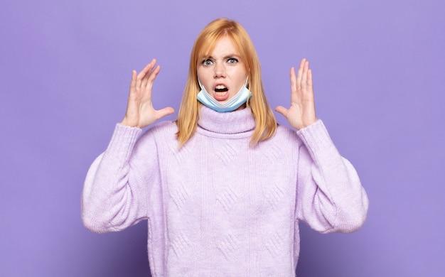 Красивая женщина кричит с поднятыми руками, чувствуя ярость, разочарование, стресс и расстройство