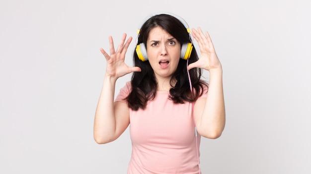 Красивая женщина кричит с поднятыми руками в воздухе, слушая музыку в наушниках