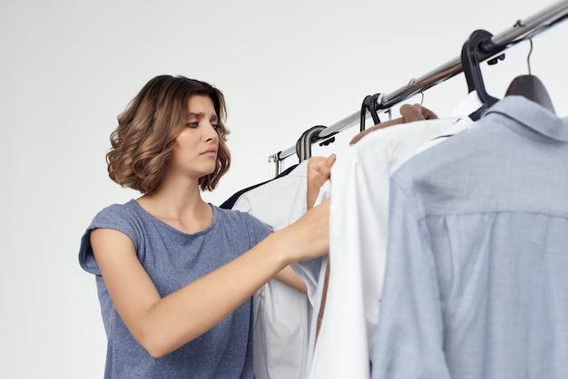 Симпатичная женщина выбор одежды возле шкафа изолированного фона