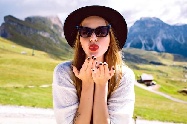 山岳リゾートでの休暇からキスを送信するきれいな女性