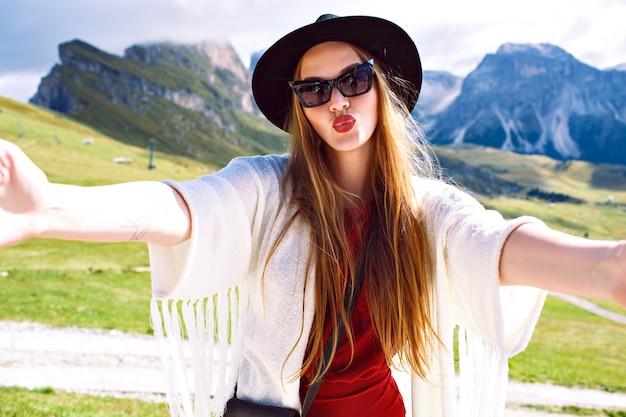 Bella donna che invia baci dalla vacanza nella località di montagna