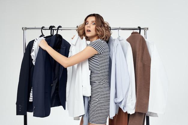 Симпатичная женщина-шопоголик, выбирая одежду, делающую покупки в магазине, изолировала фон
