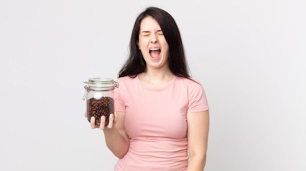 Красивая женщина агрессивно кричит, выглядит очень сердитой и держит бутылку кофе в зернах