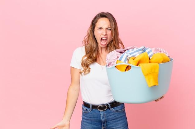 Симпатичная женщина агрессивно кричит, выглядит очень сердитой и стирает одежду.