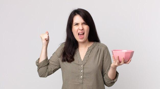 빈 냄비 그릇을 들고 화난 표정으로 공격적으로 외치는 예쁜 여자. 헤드셋이 있는 보조 에이전트