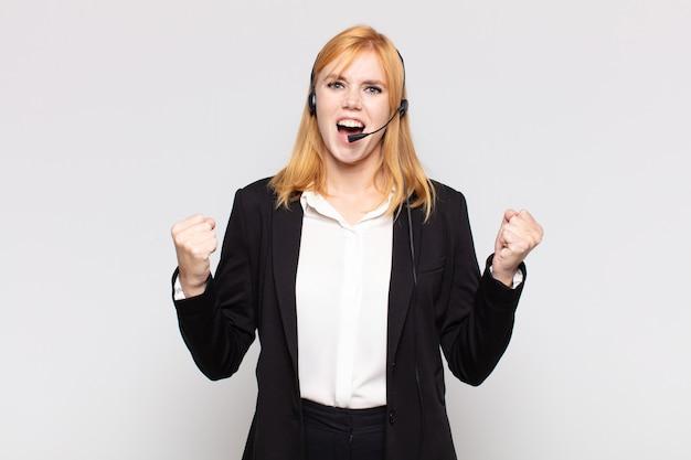 Красивая женщина агрессивно кричит с сердитым выражением лица или со сжатыми кулаками, празднуя успех