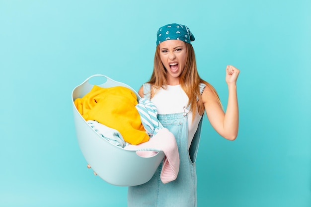 Pretty woman shouting aggressively with an angry expression holding a wash basket