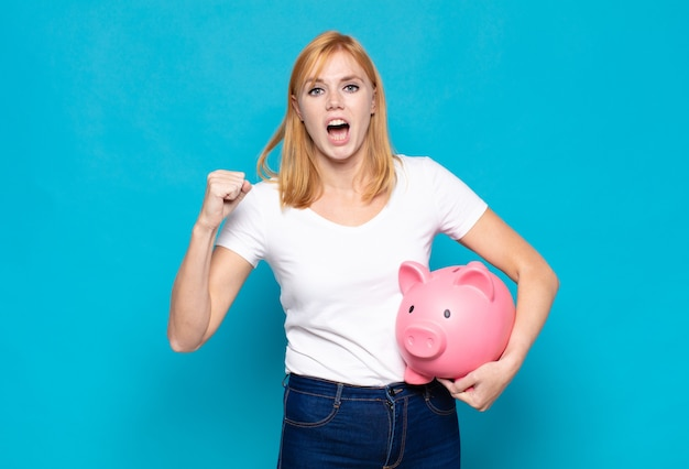 Pretty woman  shouting aggressively with an angry expression or with fists clenched celebrating success