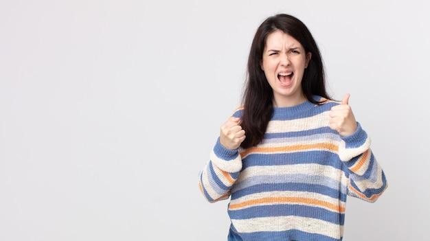 Красивая женщина агрессивно кричит с раздраженным, разочарованным, злым взглядом и сжатыми кулаками, чувствуя ярость