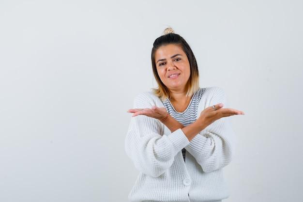 Bella donna che mostra un gesto impotente in maglietta, cardigan e sembra indecisa
