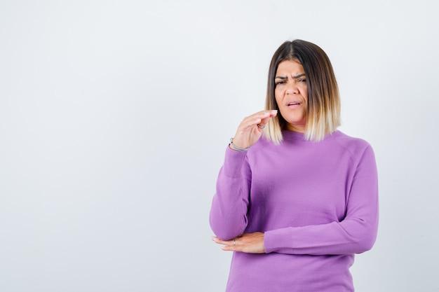 紫色のセーターで停止ジェスチャーを示し、緊張しているきれいな女性。正面図。