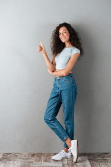 Pretty woman showing thumb up gesture isolated
