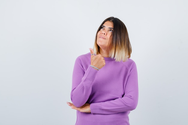 親指を上に向けて、紫色のセーターを上向きに見て、夢のような正面図を見せているきれいな女性。