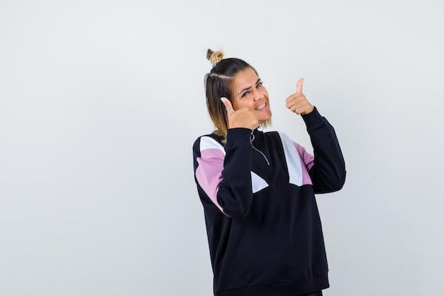 スウェットシャツに親指を立てて喜んでいるきれいな女性。