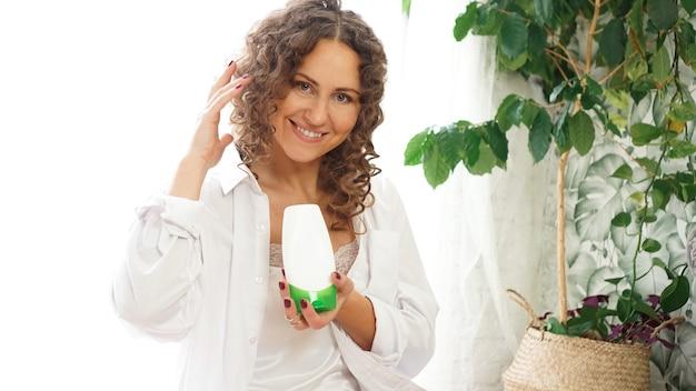 Красивая женщина показывает белую косметическую трубку для ухода за вьющимися волосами в руке дома, в белой комнате с зелеными растениями