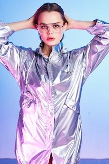 きれいな女性のシルバージャケットモダンなスタイルのナイトクラブ青い背景