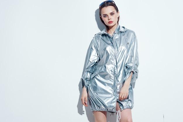 Красивая женщина в серебряных куртках на вечеринке позирует в ночном клубе
