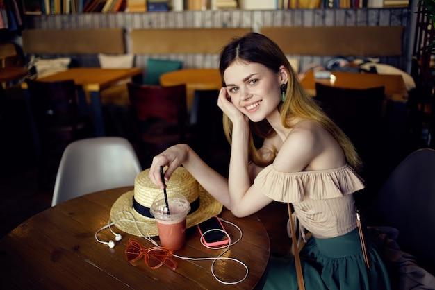 예쁜 여자는 재미 있고 음료와 함께 유리를 편안하게 레스토랑에서 테이블에 앉아
