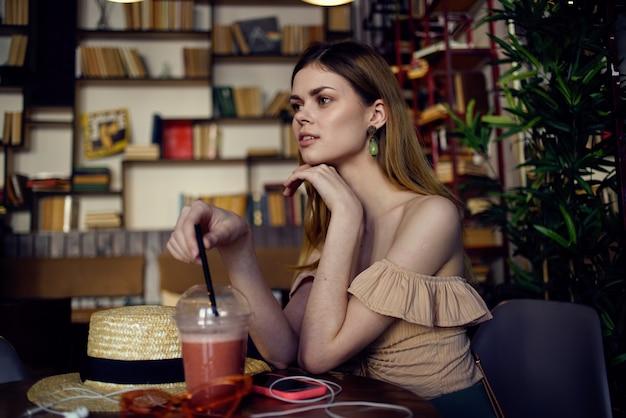きれいな女性が飲み物と一緒に楽しんでリラックスできるグラスを持っているレストランのテーブルに座っています