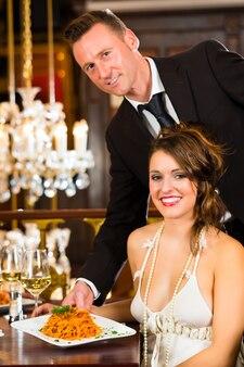 Красотка сидит за столом в ресторане изысканной кухни, ужин обслуживает официант, в люстре большая люстра