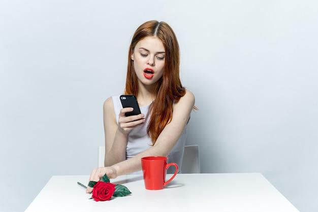 Красивая женщина сидит за столом с телефоном в руках кружка общения эмоций с напитком
