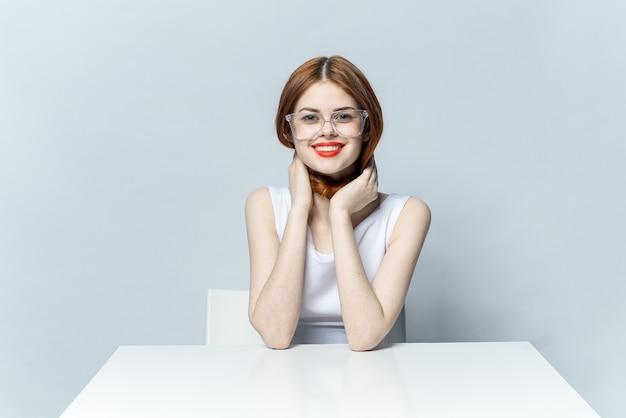 眼鏡を手に白いテーブルに座っているきれいな女性の笑顔のライフスタイル