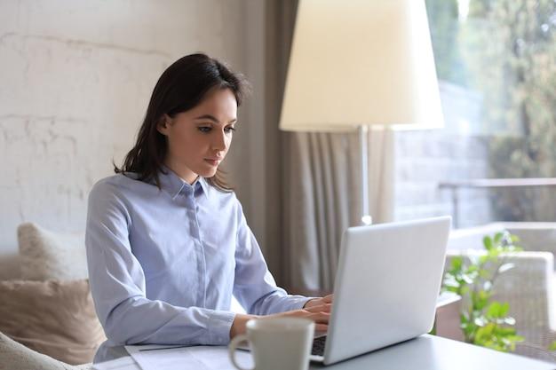 Красивая женщина сидит за столом, глядя на экран ноутбука. счастливый предприниматель читает электронное письмо с хорошими новостями, болтает с клиентами в интернете.