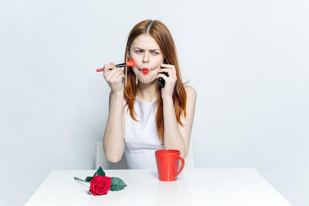 Красивая женщина, сидящая за чашкой стола с напитком, разговаривает на светлом фоне телефона. фото высокого качества