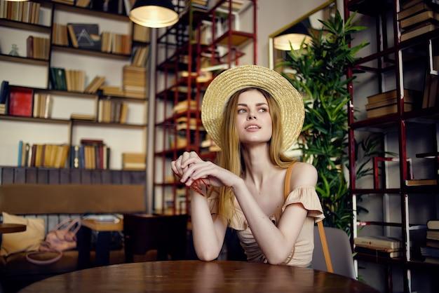 テーブルライブラリの残りの読書に座っているきれいな女性