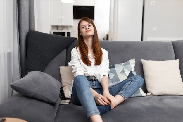 Pretty woman sitting in comfortable sofa and resting interior