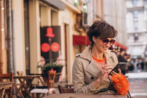 チャイナタウンのカフェに座って電話で話しているきれいな女性