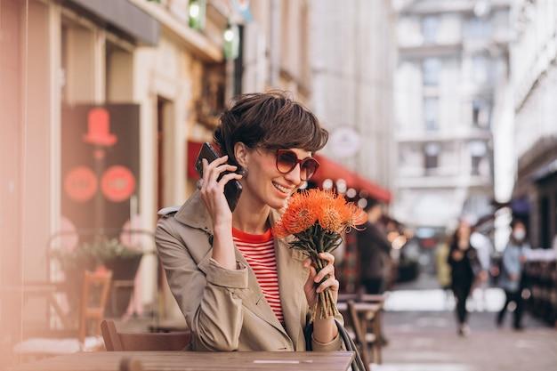 Красивая женщина сидит в кафе в китайском городе и разговаривает по телефону