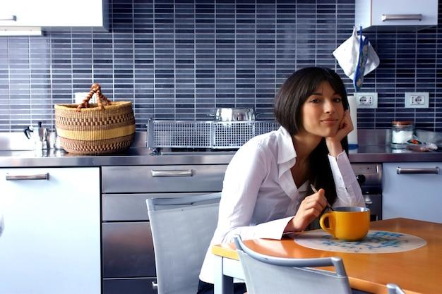 Pretty woman sitting in a kitchen