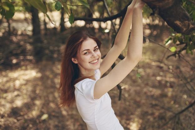 Красивая женщина, сидя рядом с деревом пейзаж. фото высокого качества
