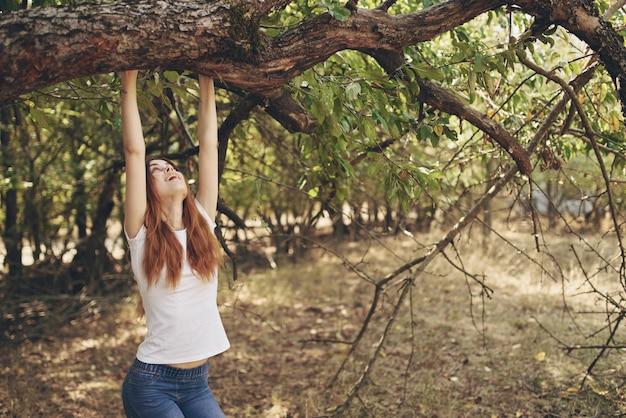 木の自然の近くに座っているきれいな女性ライフスタイルの夏。高品質の写真