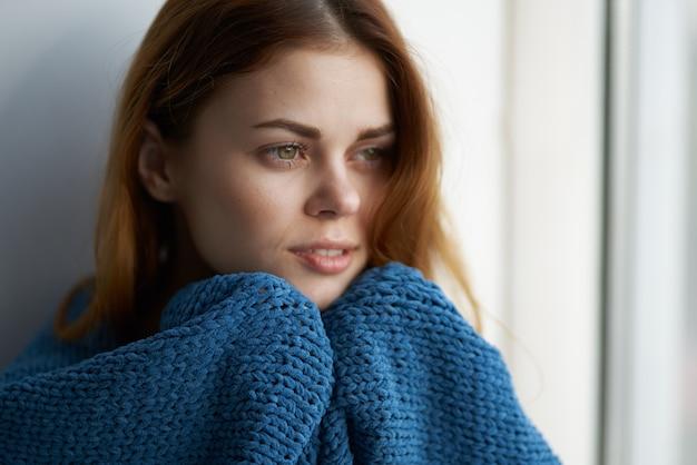 Красивая женщина, сидящая у окна с синим клетчатым образом жизни