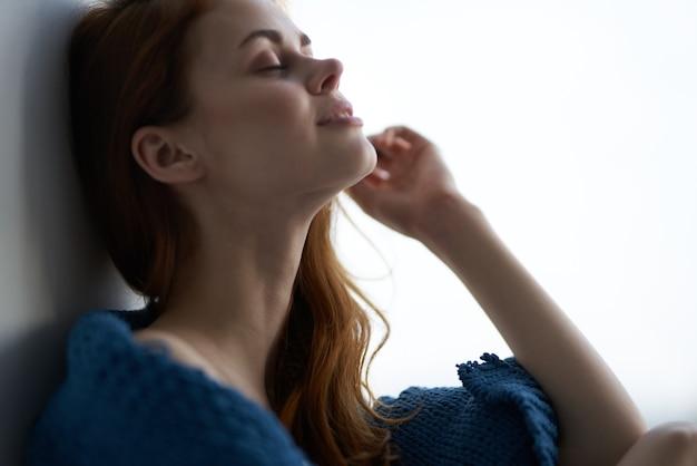 青い格子縞の休息と窓の近くに座っているきれいな女性