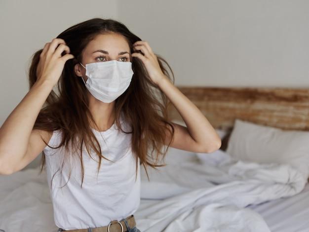 彼女の顔に医療マスクと屋内のベッドに座っているきれいな女性