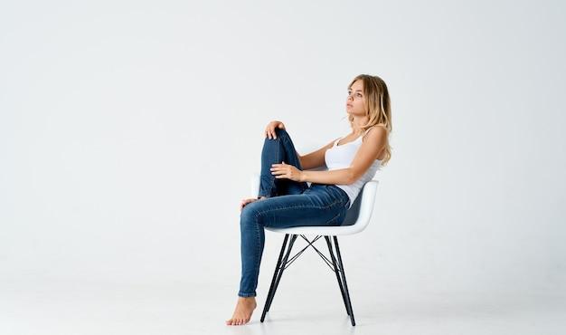 Красивая женщина сидит на стуле согнутыми ногами эмоции светлом фоне