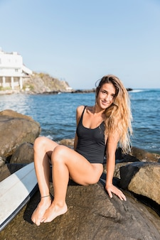 Pretty woman sitting on rock with surfboard